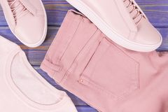 Womanly clothing and accessories on old boards, leather shoes, sweater and pants. Womanly clothing and accessories on old boards, pink leather shoes, sweater and Royalty Free Stock Image