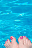 Womanly Feet Dangle in Pool. A woman's pink-pedicured feet dangle in a refreshing pool of reflecting blue water Stock Image