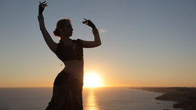 Womanly girl dancing oriental dance at sunset