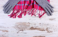 Womanly gloves and colorful shawl, copy space for text on old rustic board. Frame of womanly woolen gloves and colorful shawl, copy space for text on old rustic Royalty Free Stock Photo