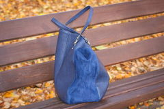Womanly handbag on bench in autumn park. Womanly leather blue handbag lying on bench in autumn park Royalty Free Stock Photos