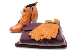 Womanly leather shoes, gloves and clothes on white background Royalty Free Stock Image
