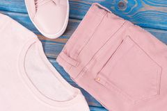 Womanly leather shoes, sweater and pants on old blue boards. Womanly pink leather shoes, sweater and pants lying on old blue boards Stock Photo
