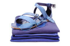 Womanly sandals and sunglasses on pile of blue clothes. White background Royalty Free Stock Photography