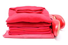 Womanly shoes and pile of red clothes. White background Royalty Free Stock Photo