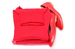 Womanly shoes and pile of red clothes. White background Royalty Free Stock Photography