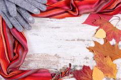 Womanly woolen clothes and autumnal leaves with copy space for text, old rustic wooden background Royalty Free Stock Photography