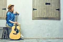 Womann que se sienta en banco con la guitarra Fotos de archivo