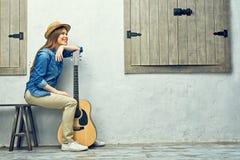 Womann que se sienta en banco con la guitarra Foto de archivo
