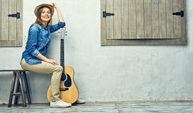 Womann que se sienta en banco con la guitarra Imágenes de archivo libres de regalías