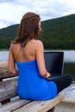 Womann que trabalha em um portátil em um lago foto de stock