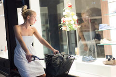 Womanon bicycle window shopping at night. Royalty Free Stock Photos