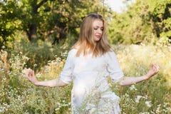 Womanr incinto dei giovani un giorno di estate sulla natura Fotografia Stock