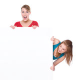 Womans with banner. Full isolated studio picture from two young woman with white copyspace sign (banner royalty free stock images