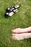 Womans bare feet on green grass Stock Photo