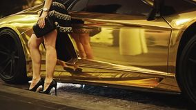 Womans Bare Legs in Heels standing in front of a Gold Lamborghini stock video