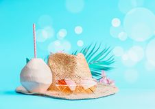 Womans beach accessories with fresh coconut, drinking straws and tropical leaves and flowers , sunglasses and straw hat on sunny. Blue background with bokeh stock photography