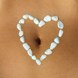 Womans belly with heart made of white pebble stones. Womans belly closeup with heart made of white pebble stones around the belly bottom Stock Image