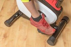 WomanÂs ben på motionscykelen inomhus horisontal Arkivfoto