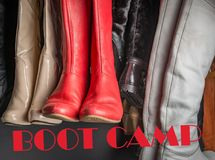 A different Boot camp. Womans boot hanging in a group with the word bootcamp in Background Stock Image