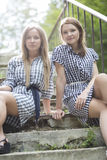 Womans in checkered dresses sit on stairs Royalty Free Stock Photo
