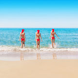 Womans in christmas hats on sea beach Royalty Free Stock Photos