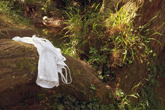 A womans clothing left beside a river while she is swimmming Stock Image