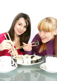 Womans eating  sushi. A pretty young  womans eating salmon sushi with chopsticks Royalty Free Stock Photo