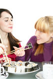 Womans eating  sushi. A pretty young  womans eating salmon sushi with chopsticks Royalty Free Stock Photography