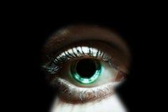 Womans eye peeking through a keyhole Royalty Free Stock Images