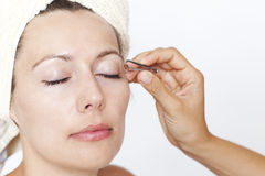Woman's eyebrows being plucked Royalty Free Stock Photos