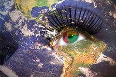 Womans face with planet Earth texture and guinea bissau flag inside the eye. Stock Image