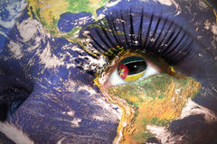 Womans face with planet Earth texture and mozambican flag inside the eye. Royalty Free Stock Photo