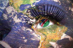 Womans face with planet Earth texture and namibian flag inside the eye. Royalty Free Stock Photo
