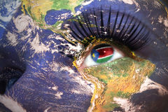 Womans face with planet Earth texture and South Sudan flag inside the eye. Royalty Free Stock Photos