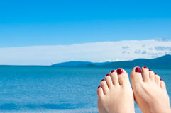 Womans feet against sea and blue sky Royalty Free Stock Photos