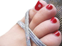 Womans feet in the footwear with decorated painted nails Stock Photos
