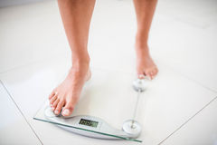Womans feet going on weighting scale. At home Stock Photos