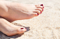 Womans feet on sand Stock Photos
