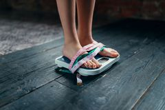Womans feet on the scales tied with measuring tape. Fat or calories burning concept. Weight loss, hard dieting Stock Photos