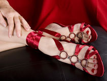 Womans feet in sexy shoes. On leather pillow Royalty Free Stock Photography
