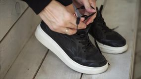Womans feet are shod in black sporty shoes, hands are tying shoelaces, close-up. Close-up of hands of young girl, tying laces on sneakers. She is fastenings knot stock video