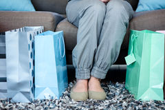 Womans feet surrounded by gift bags Stock Photo