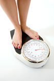 Womans feet on weighing scales Royalty Free Stock Images