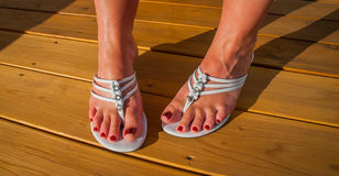 Womans feet in white tri strap summertime sandals on new wooden deck. Stock Images
