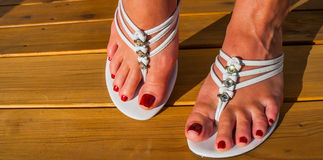 Womans feet in white tri strap summertime sandals on new wooden deck. Royalty Free Stock Photography