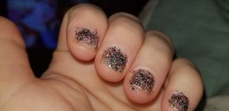 Womans hand with sparkly nail polish royalty free stock photos