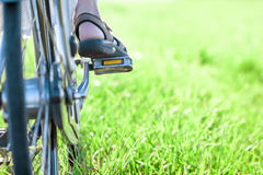 Womans foot on bicycle pedal on green grass closeup Stock Photos