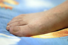 Womans foot on the blue and yellow background Royalty Free Stock Photography