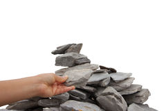 Woman's hand adding a rock to a cairn Royalty Free Stock Photography